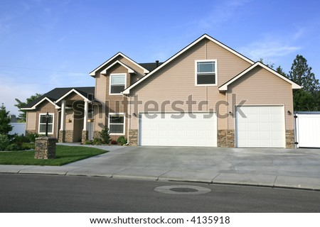 Two tone beige two story home with three car garage - stock photo