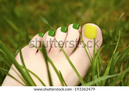 Two-tone pedicure yellow and green colours on the background of grass  - stock photo