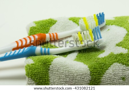 two toothbrush with green towel on isolate white background - stock photo