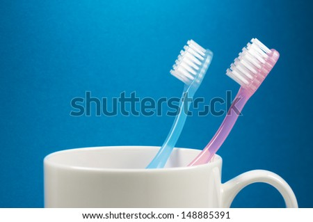 Two toothbrushes and a cup. (horizontal) Brushes on blue background.