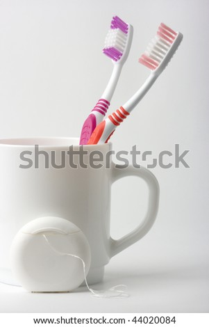 Two toothbrushes in a cup and dental floss - common toiletries - stock photo