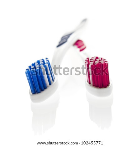 Two toothbrushes (pink and blue) isolated on a white background. - stock photo