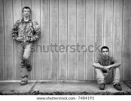 Two tough-looking teen boys hanging out against a wall. - stock photo