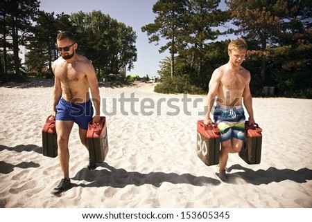 Two tough young male  lifting heavy jerrycans and walking during a  workout on the beach. - stock photo