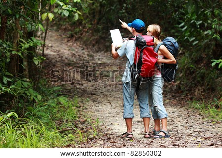 Two tourist looking for a road with map and clock in the forest with backpack - stock photo