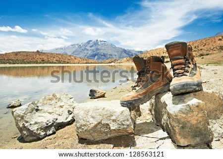 Two tourist traveller hiker shoes boots standing on stones near lake in Himalayas mountains - stock photo