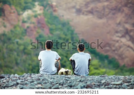 Two tourist young men sitting on rocky cliff and enjoying beautiful view - stock photo