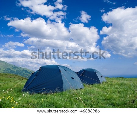 two touristic tents in a field - stock photo