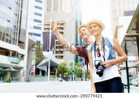 two tourists calling for a taxi in the city - stock photo