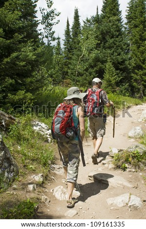 Two tourists make hiking the trail in the woods - stock photo