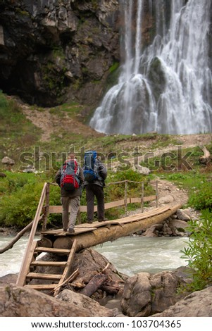 Two tourists man and woman walking to waterfall - stock photo