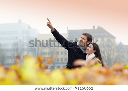 Two tourists on vacation discovering a city in autumn - stock photo