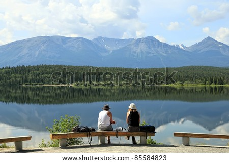 Two tourists sit on a bench about mountain lake and look at reflection of mountains in quiet water