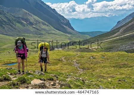 two tourists walking on mountain valley in tunka range, Siberia
