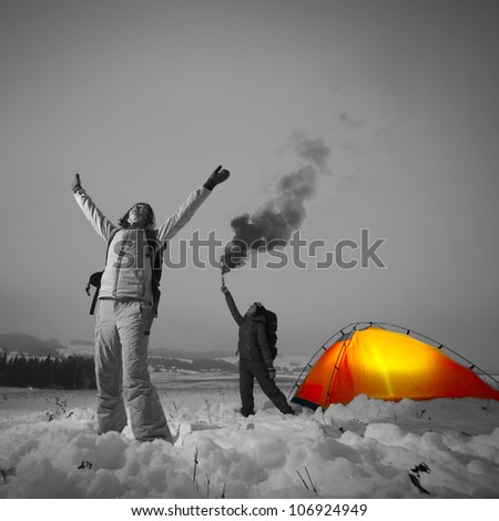 Two tourists with backpacks asking a help in a winter field