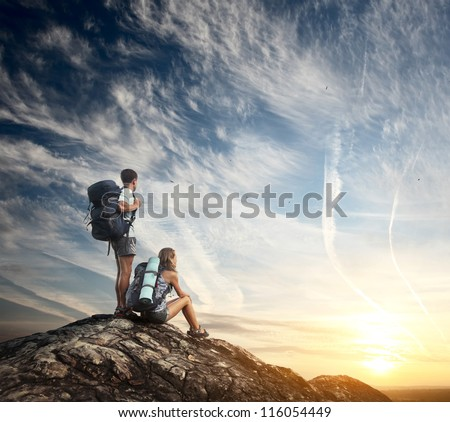 Two tourists with backpacks enjoying sunset on top of a mountain - stock photo