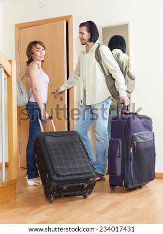 Two tourists with luggage near the door in a nice house