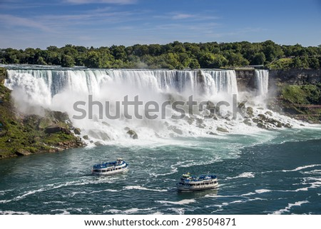 Two tours boats on the Niagara River pass in front of the American Falls in Niagara Falls New York. The photo was taken from Niagara Falls Ontario Canada. - stock photo