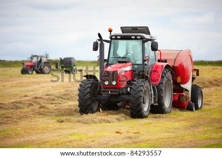 two tractors collecting haystack in the field at nice blue sunny day