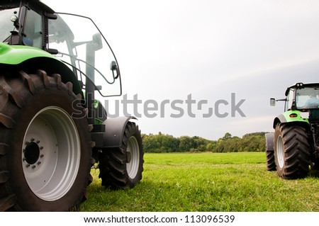 two tractors on the green field - stock photo