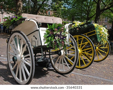 Two traditional  dutch cabriolet  carriages beautiful decorated with flowers are waiting for their horses