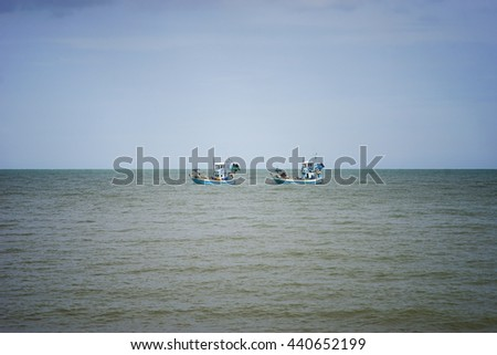two traditional fishing boat sailing on the sea, blue sky background