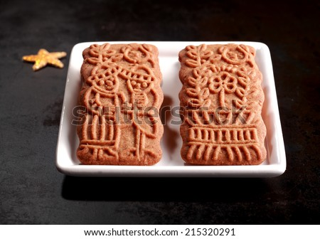 Two traditional spicy crisp Dutch speculoos biscuits, a speciality baked for the feast of St Nicholas and now consumed worldwide for Christmas - stock photo