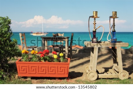 Two traditional turkish waterpipes (nargile) on the table in outdoor restaurant with view on Mediterranean sea in Kemer, Turkey. - stock photo