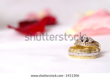 Two traditional wedding bands on white with rose petal backdrop. - stock photo