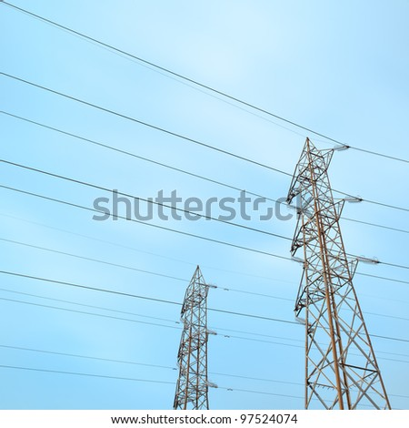 Two transmission towers, also known as electricity pylons with parallel wires.