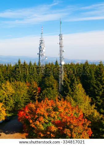 Two transmission towers in autumn forest, Czech Republic - stock photo
