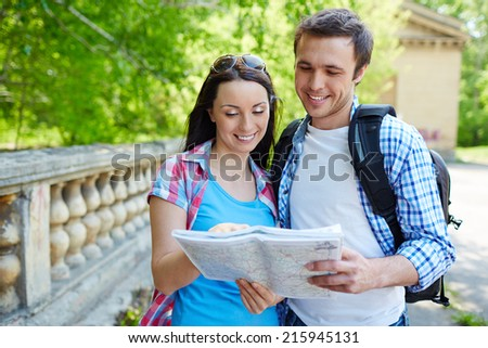Two travel lovers studying map of ancient town - stock photo