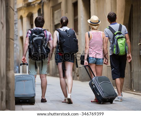 Two traveler couples with travel bags walking through the city. Back view - stock photo