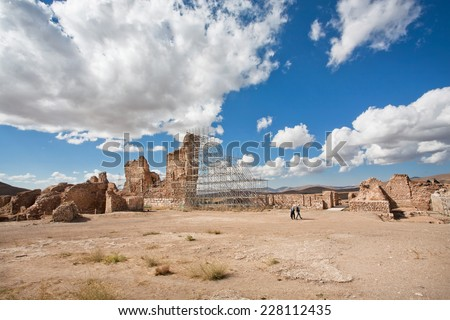 Two travelers followed by Zoroastrian fire temple Takht-e Soleyman in the mountains of Iran under white clouds. Takht-e Soleyman is an archaeological site, recognized as a UNESCO World Heritage Site - stock photo