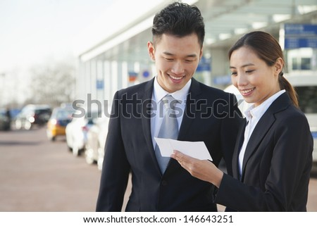 Two travelers looking at ticket in airport