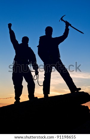 Two travelers reached tops on sunset background - stock photo