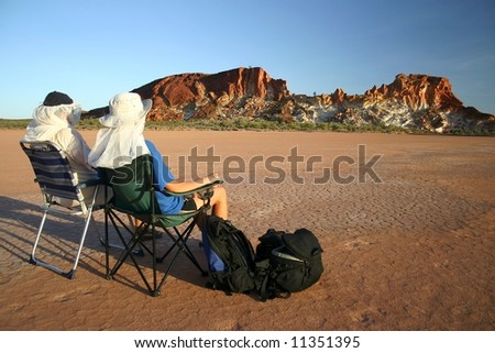 Two trekkers enjoying by the view on parched grounds with famous red rocks in background. Rainbow valley, Southern Northern Territory, Australia - stock photo