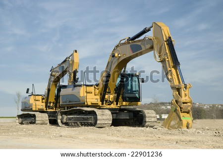 Two trench digging excavator lined-up on a construction job site.