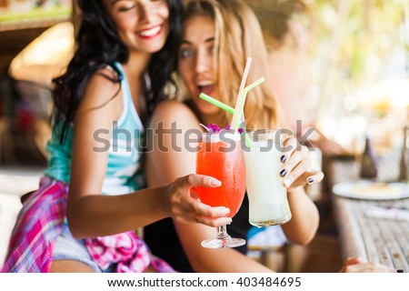 Two trendy cool hipster girls, friends, the blonde and the brunette drink cocktails at the cafe on the beach. Dressed in colorful shirts and shorts. - stock photo