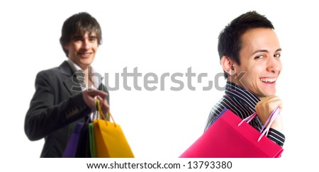 Two trendy handsome guys are smiling and they are holding some shopping bags. They are wearing stylish shirts. - stock photo