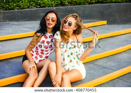 Two trendy hipster cool tanned bold girl, and ride in the shopping cart. Dressed in colorful T-shirts with his lips and pineapple, shorts, sunglasses.  Shopping. - stock photo