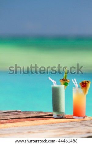 Two tropical cocktails near swimming pool and beach