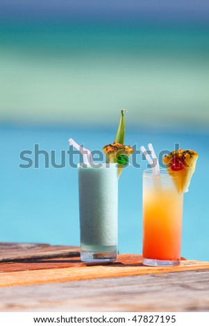 Two tropical cocktails near swimming pool and beach - stock photo