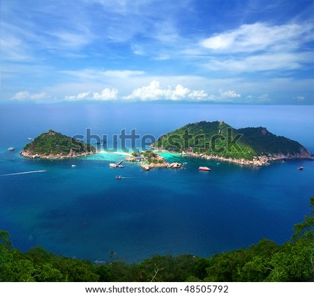 Two tropical islands at ocean on the background of the fantastic sky. - stock photo