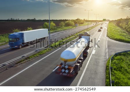 Two trucks in motion blur on the freeway towards the setting sun. Rush hour on the motorway near Belgrade - Serbia. - stock photo
