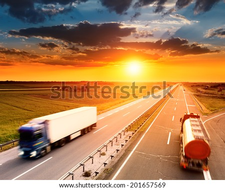 Two trucks in motion blur on the highway at sunset - stock photo
