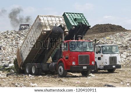 Two trucks unloading garbage at dumping ground - stock photo