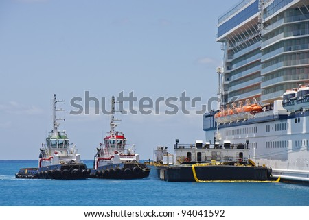 Two tugboats and a barge tied up to a cruise ship - stock photo