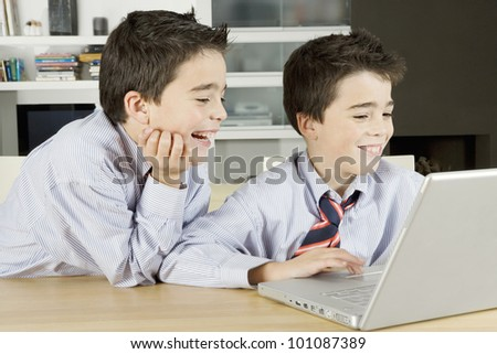 Two twin brothers sharing a laptop computer at home, laughing. - stock photo