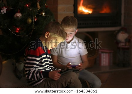 Two twin brothers sitting at the fireplace on a cozy winter evening nearby the christmas tree choosing gifts from online catalog or playing with tablet pc and smart phone - stock photo